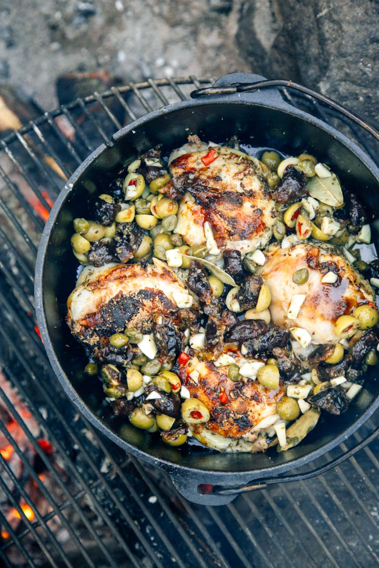 Chicken Marbella in a Dutch oven over a campfire