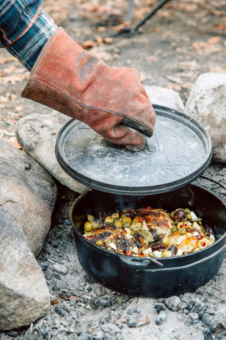 Michael lifting the lid off of a Dutch oven in a campfire