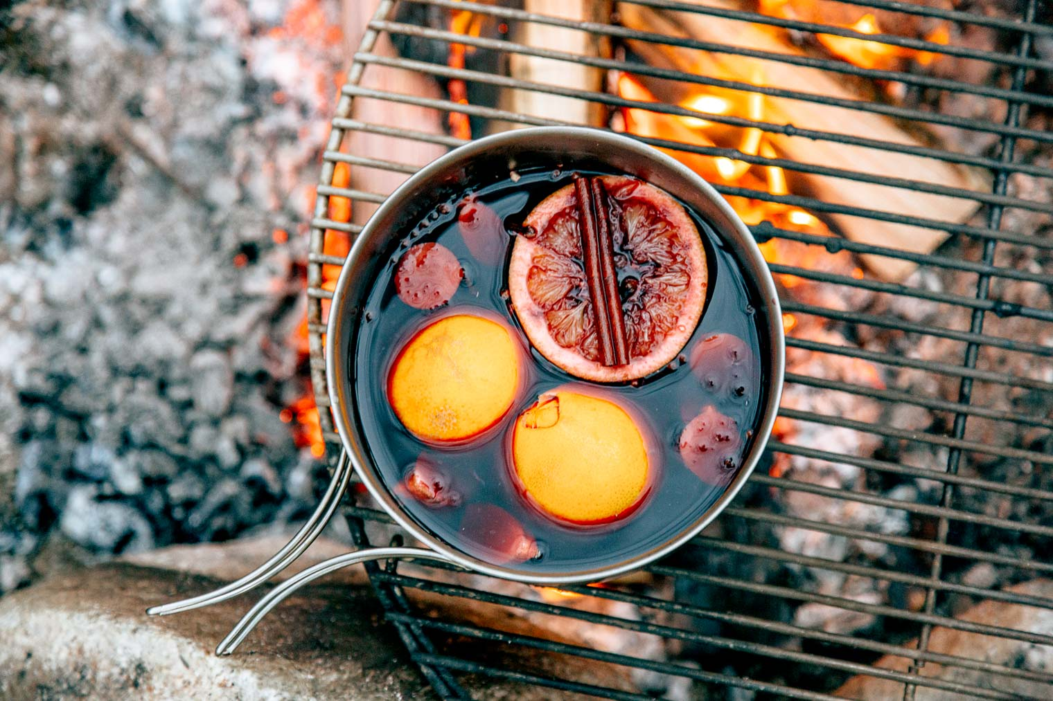 A pot of mold wine with oranges and cinnamon sticks sitting on a campfire