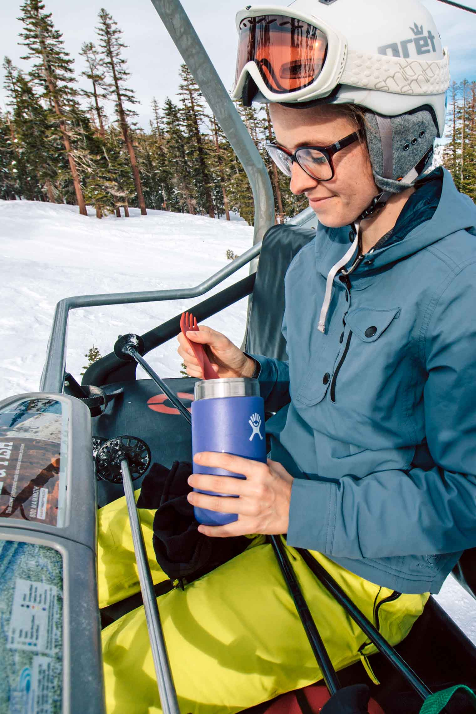 Megan eating from a insulated food container while on a ski lift