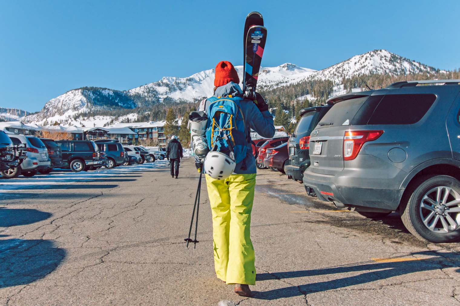 Megan carrying skis in a parking lot