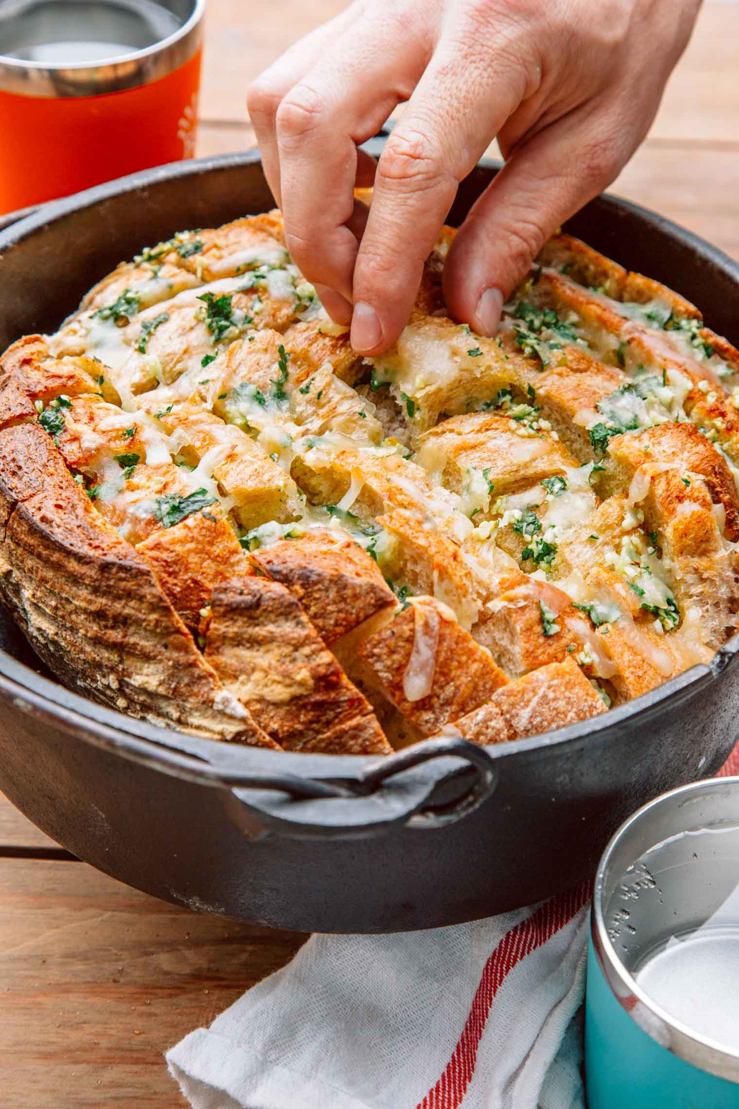A hand picking up a piece of pull apart garlic bread in a Dutch oven