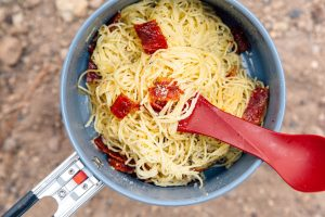 A creamy pasta dish topped with crunchy bacon jerky, pasta carbonara is a quick and easy one pot meal to make on your next backpacking trip