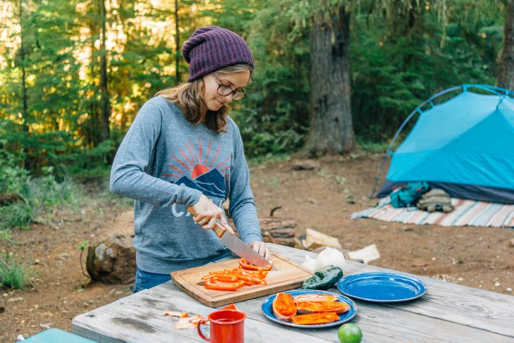 Megan standing at a camp table chopping red bell peppers on a wooden cutting board