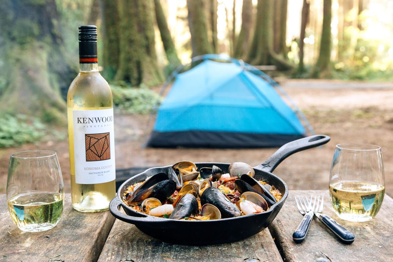 Paella in a cast iron skillet on a camp table with a vlue tent in the background