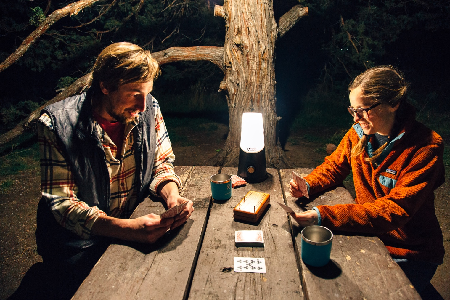 Megan and Michael playing cards at a table lit by a lantern