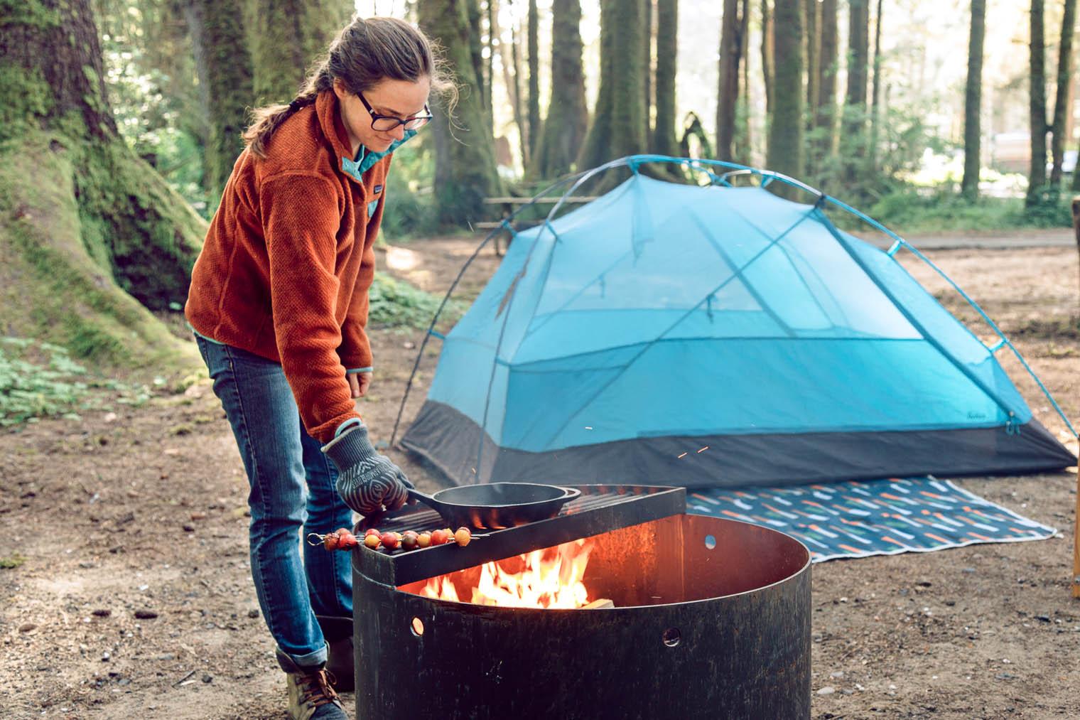 Megan moving a skillet over a campfire