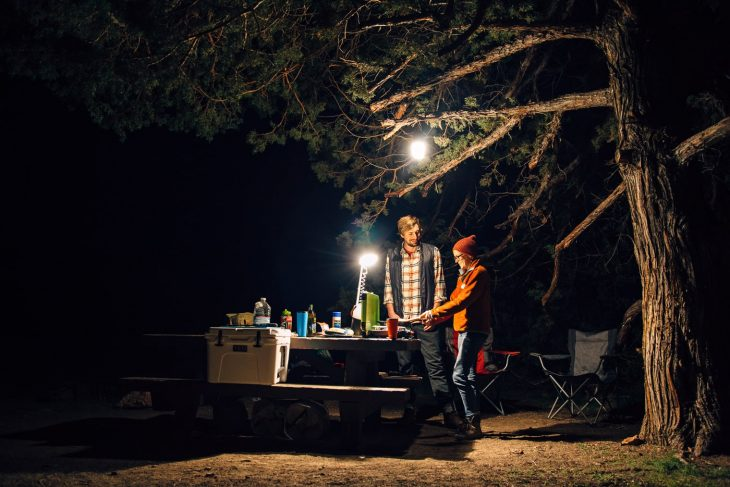Megan and Michael cooking at a campsite lit by a lantern