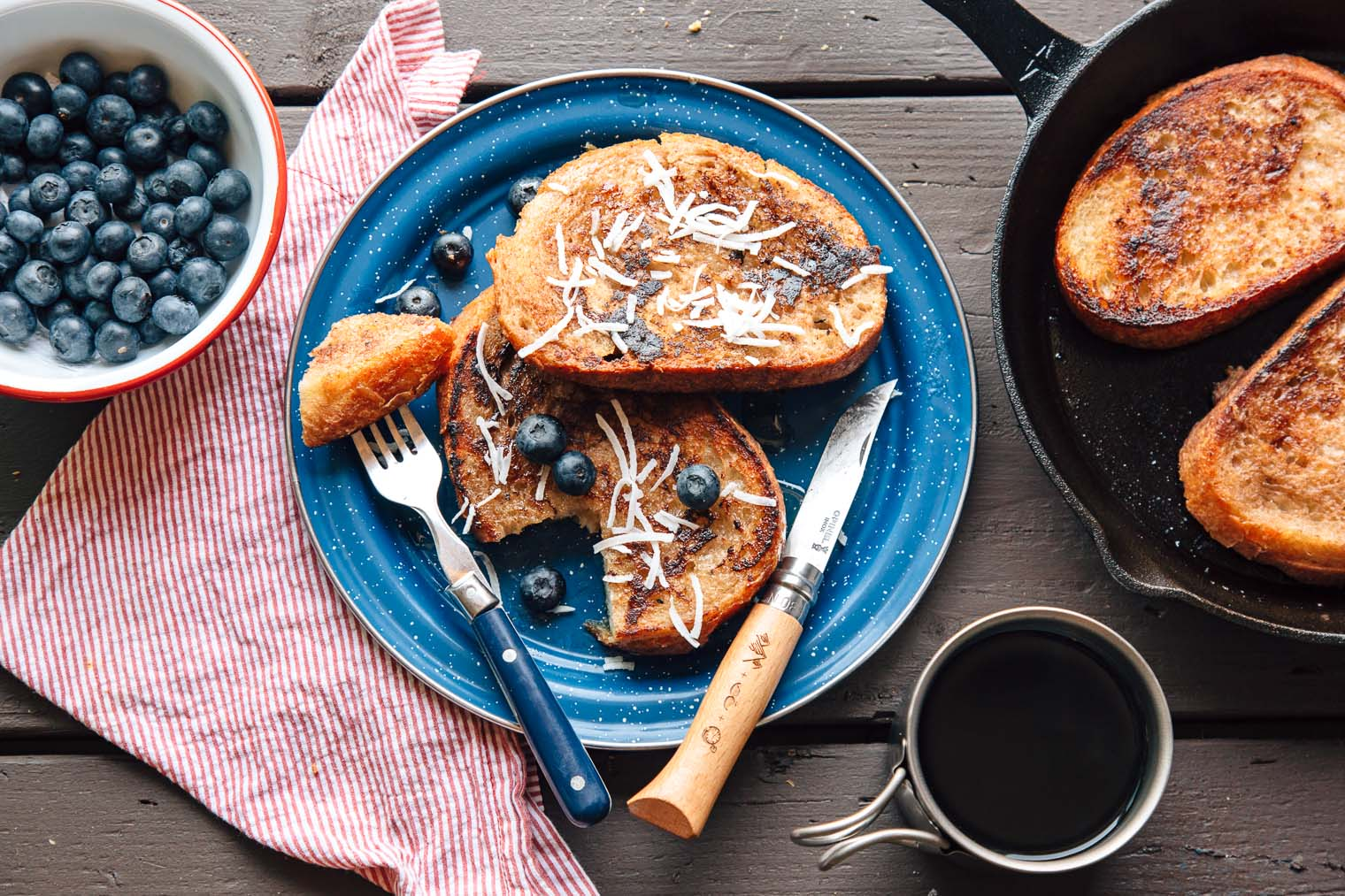 Three pieces of French toast on a blue enamel plate