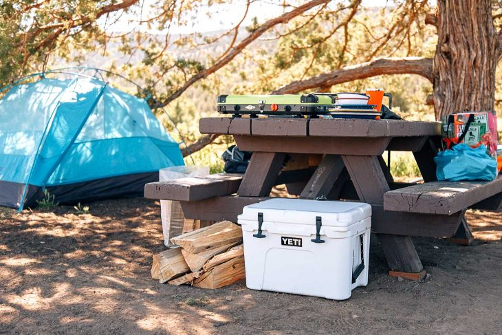 A camping scene with a white cooler next to a picnic table
