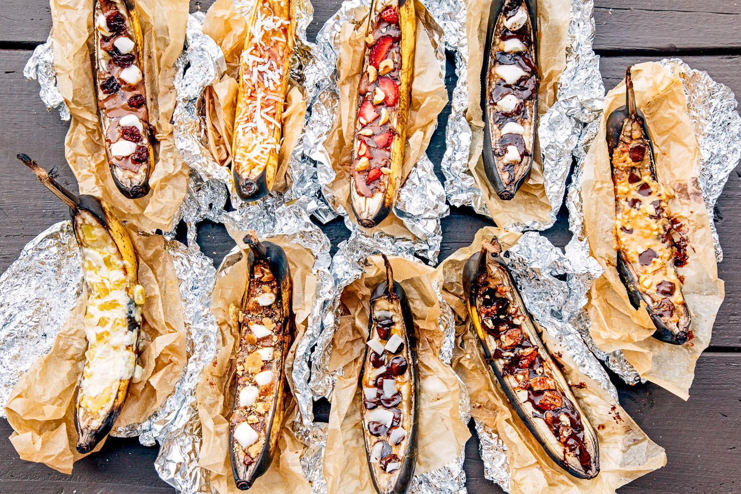 9 banana boats wrapped in foil with different toppings