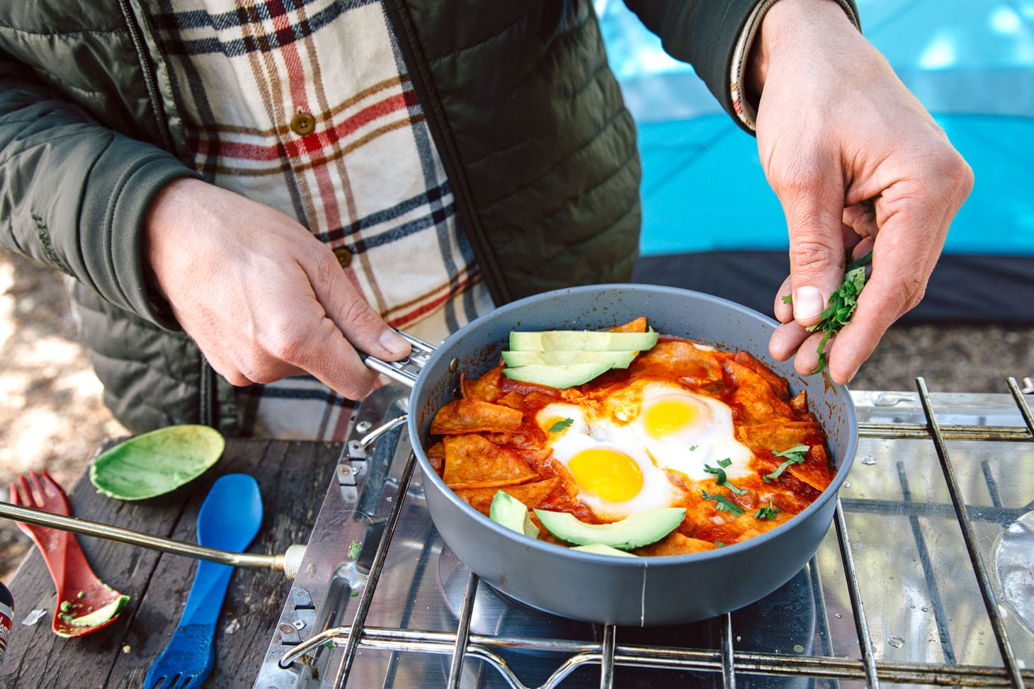 Michael is sprinkling chopped cilantro into a skillet full of Chilaquiles
