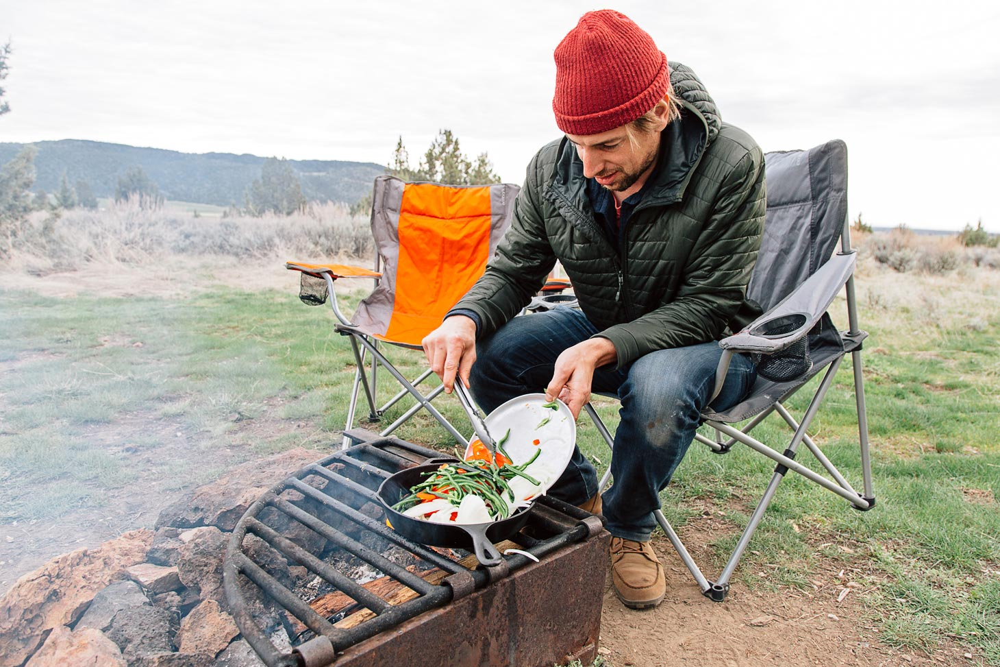 Michael adding sliced peppers into a cast-iron skillet over a campfire