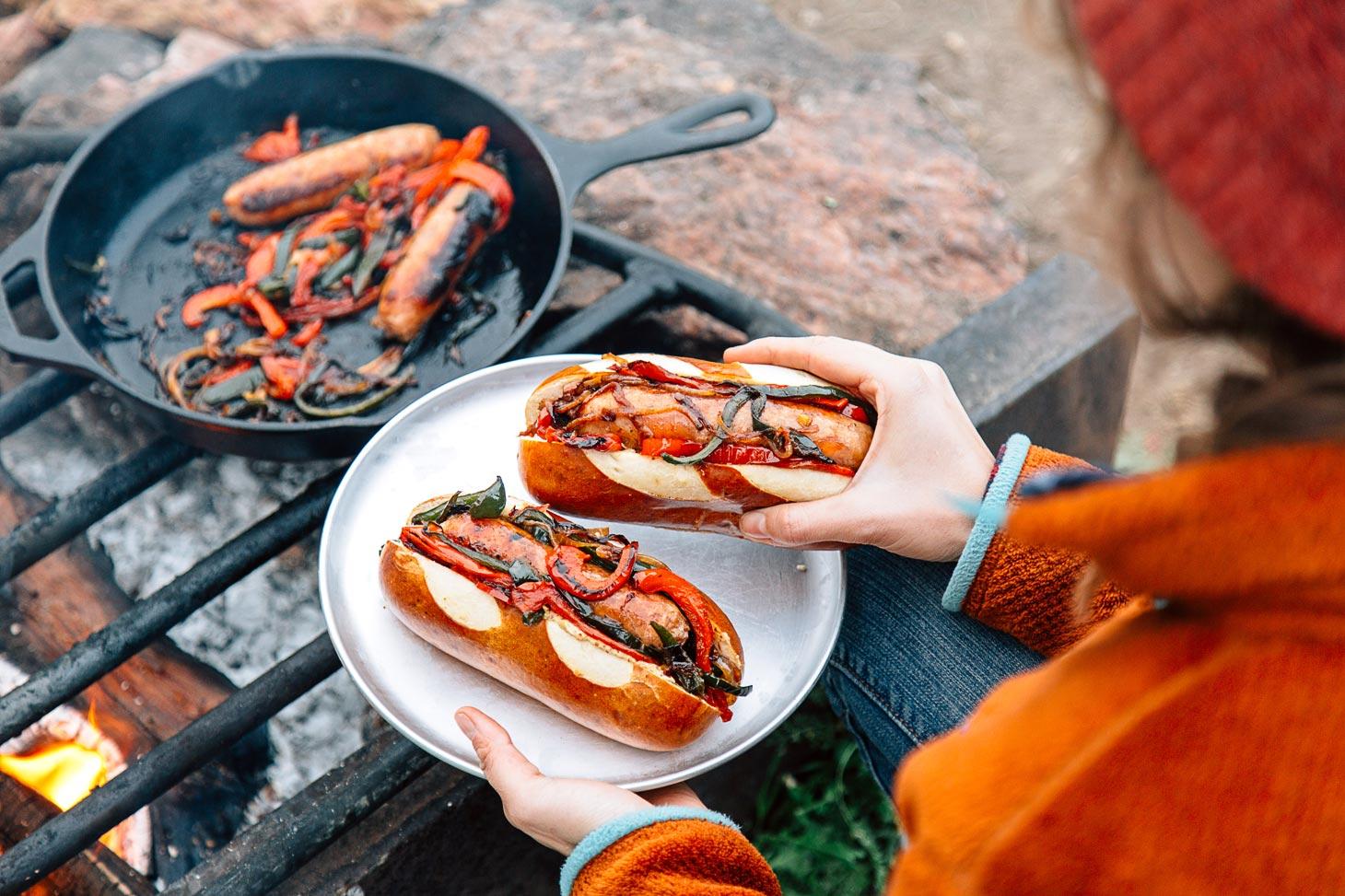 Megan holding a plate with a bratwurst in a pretzel bun near a campfire.