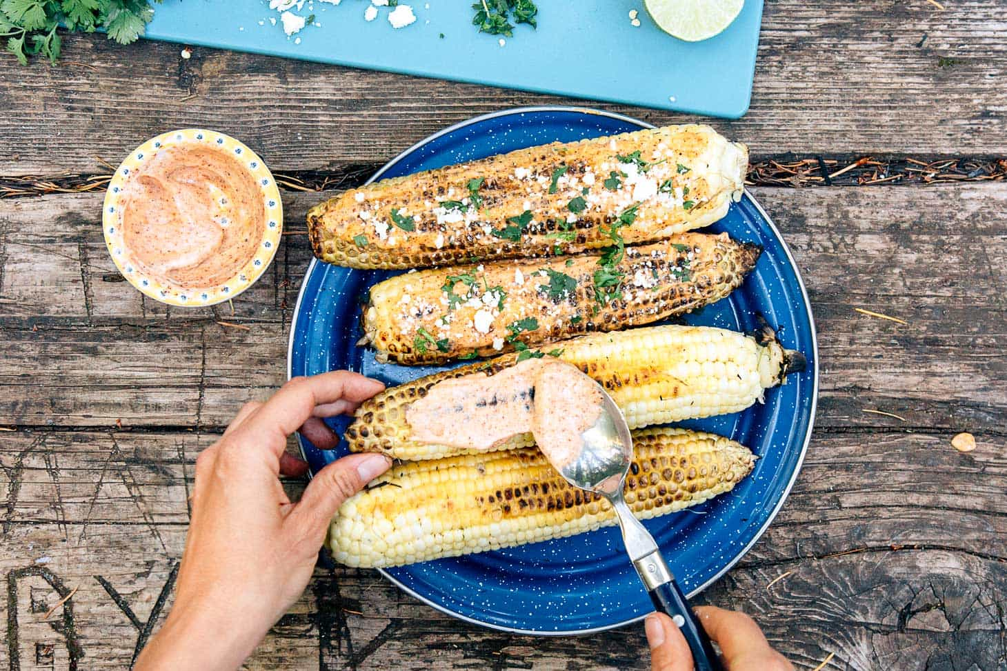Making elote - grilled corn served with spicy mayo and Cojita cheese - a perfect camping appetizer.