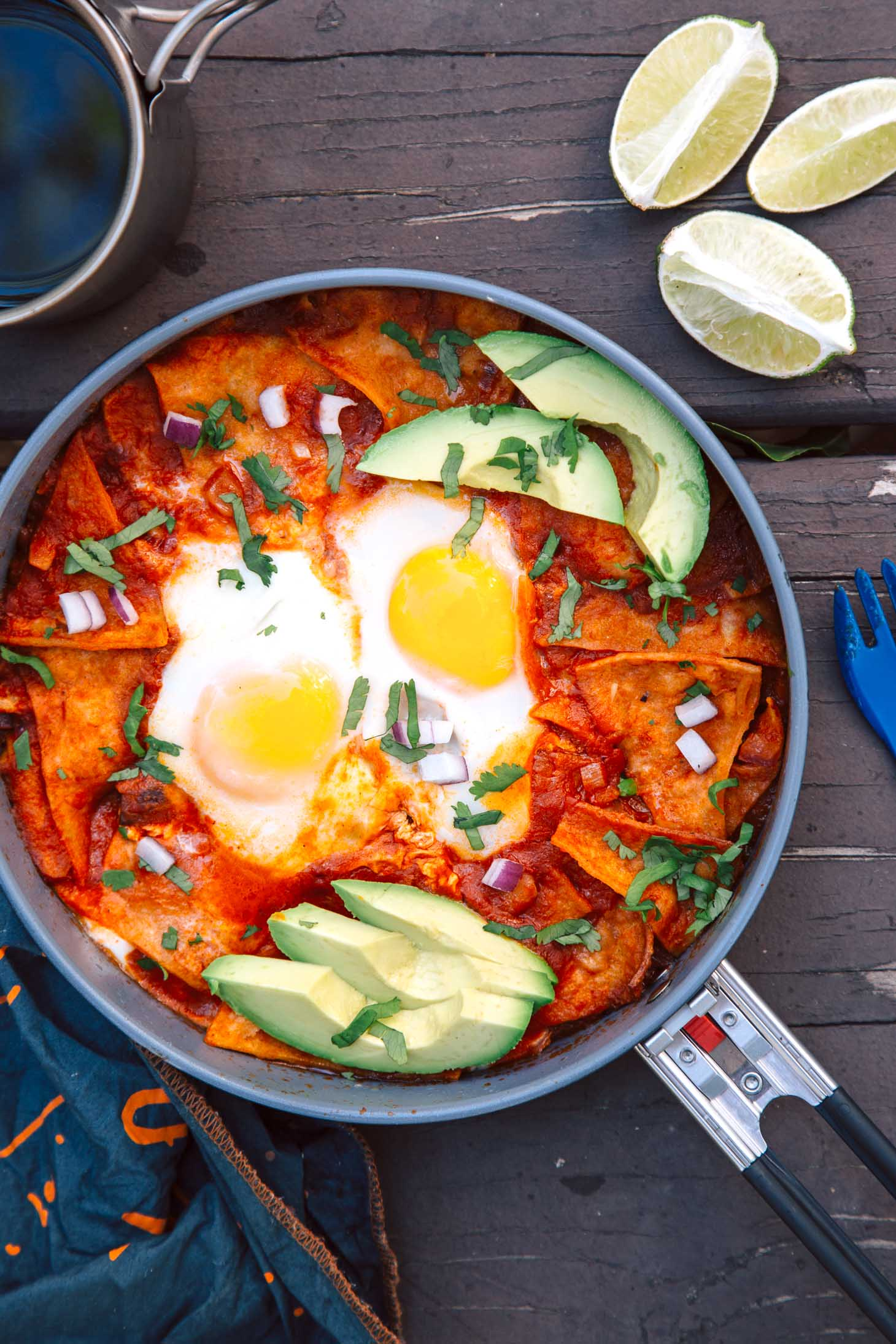 Chilaquiles with eggs and avocados in a pan on a camping table.