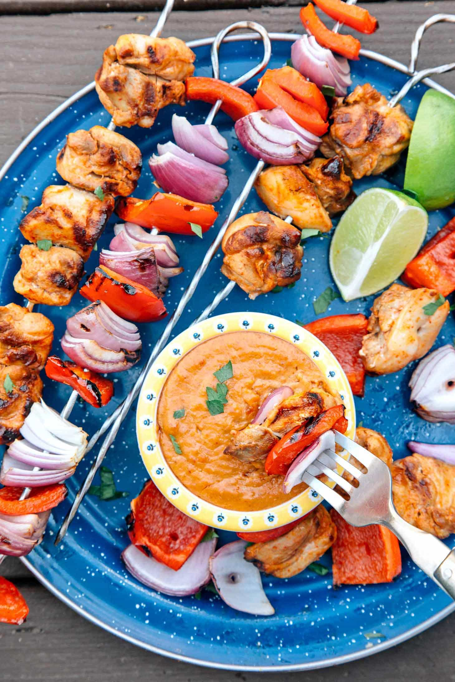 Thai grilled chicken skewers on a blue camping plate with a small bowl of peanut dipping sauce.