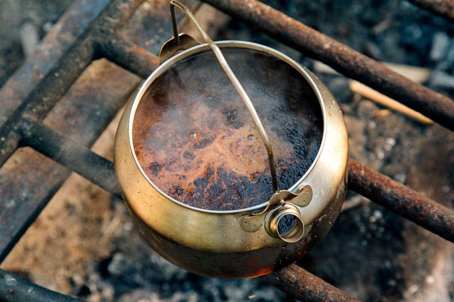 A pot of cowboy coffee on a campfire