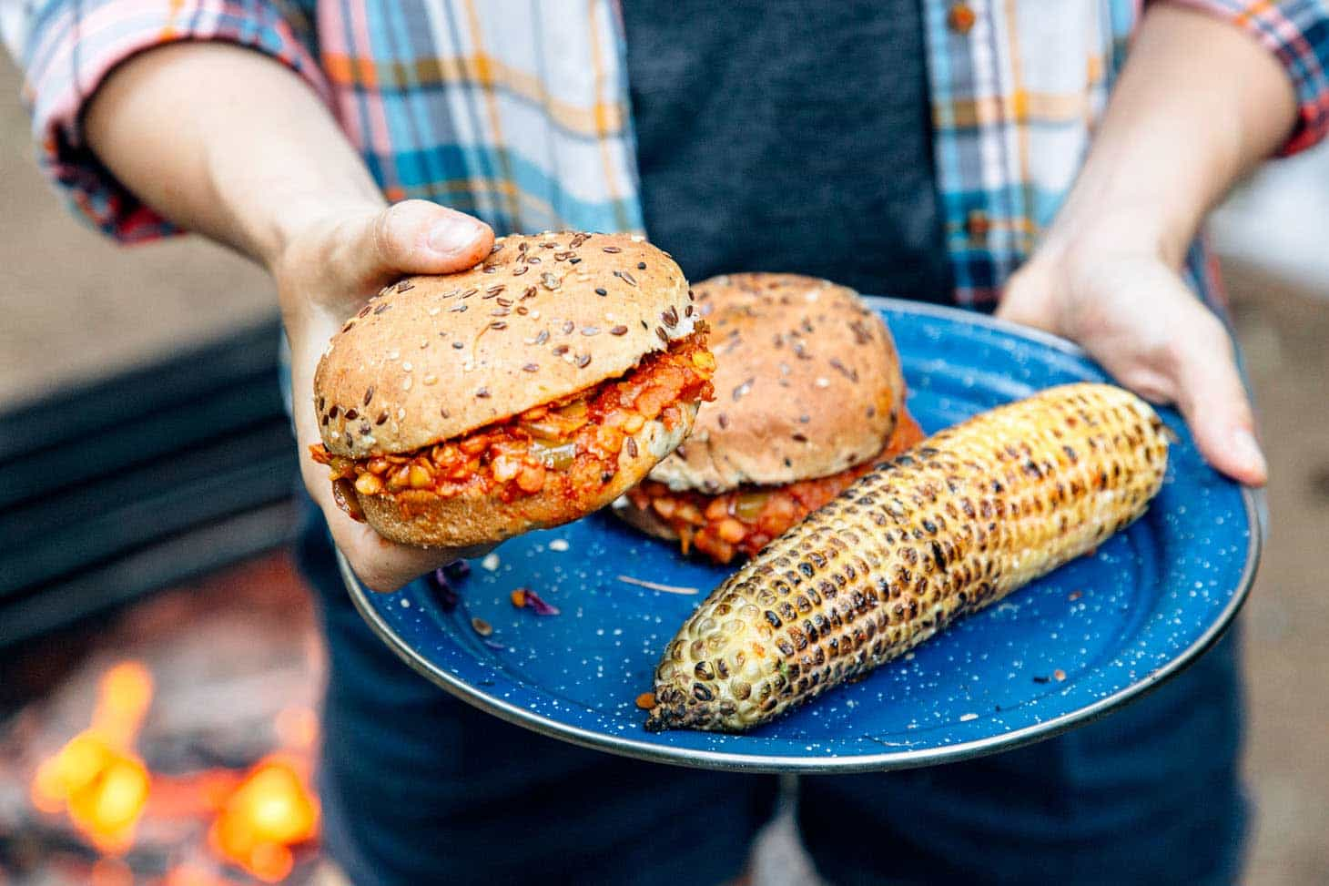 Red lentil sloppy joes on a blue camping plate with grilled corn.