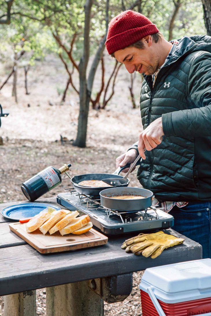 Michael cooking French toast on a camp stove with trees in the background