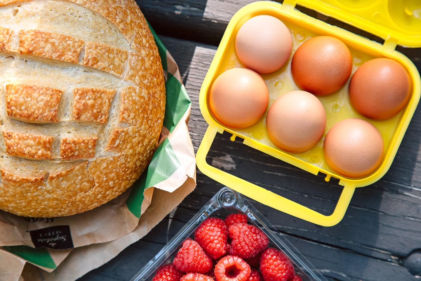 Ingredients for French toast including a loaf of bread and eggs in a yellow crate