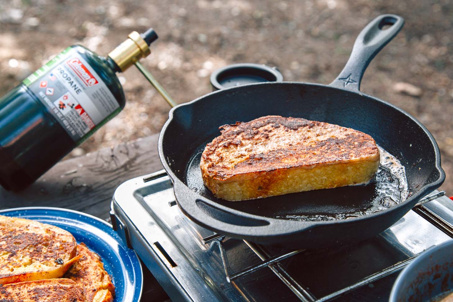 A slice of french toast in a skillet on a camp stove