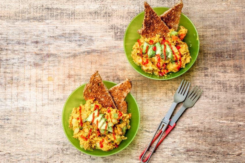 Chickpea breakfast scrambles in green bowls on a wooden surface