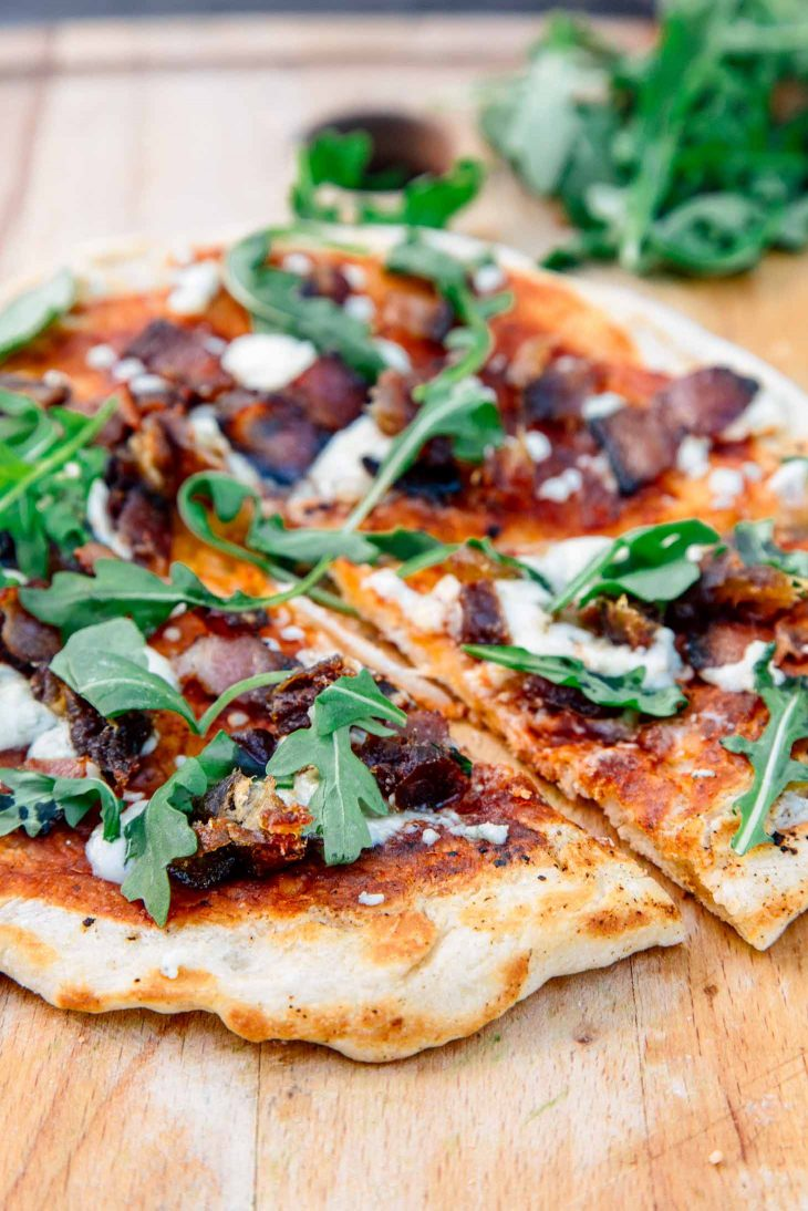 Campfire pizza on a wooden board.