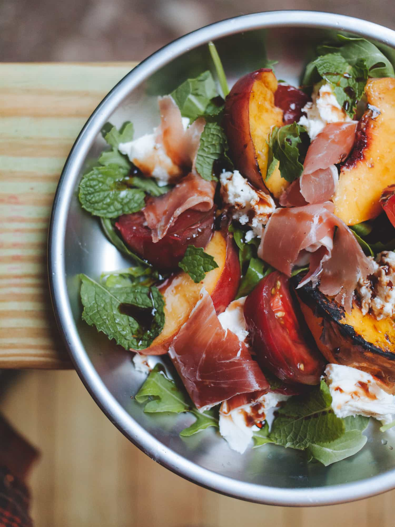 Grilled peach caprese salad on a silver camping plate.