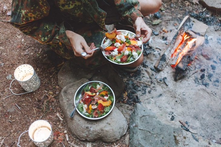 Person holding a plate of peach caprese salad next to a campfire