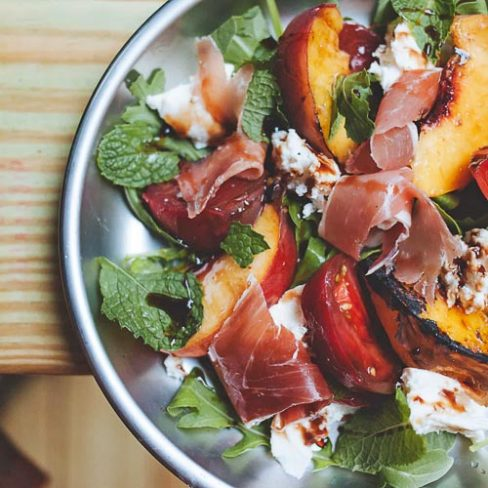 Caprese salad with grilled peaches on a plate
