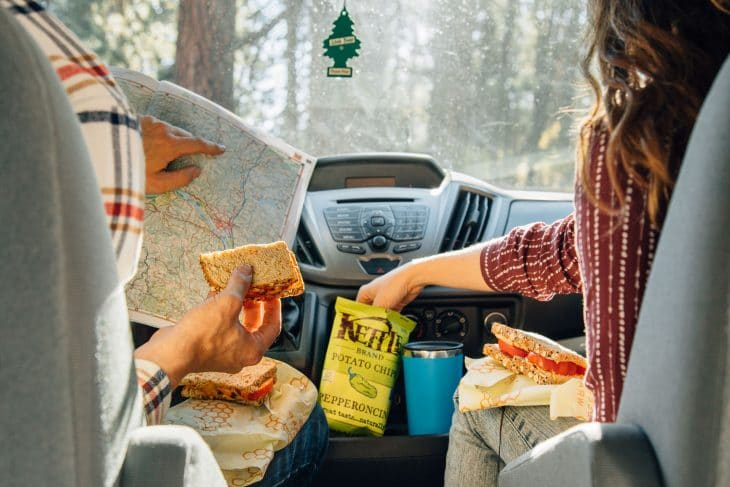 Megan sitting in a van reaching into a bag of chips. Michael is holding a sandwich and reading a map