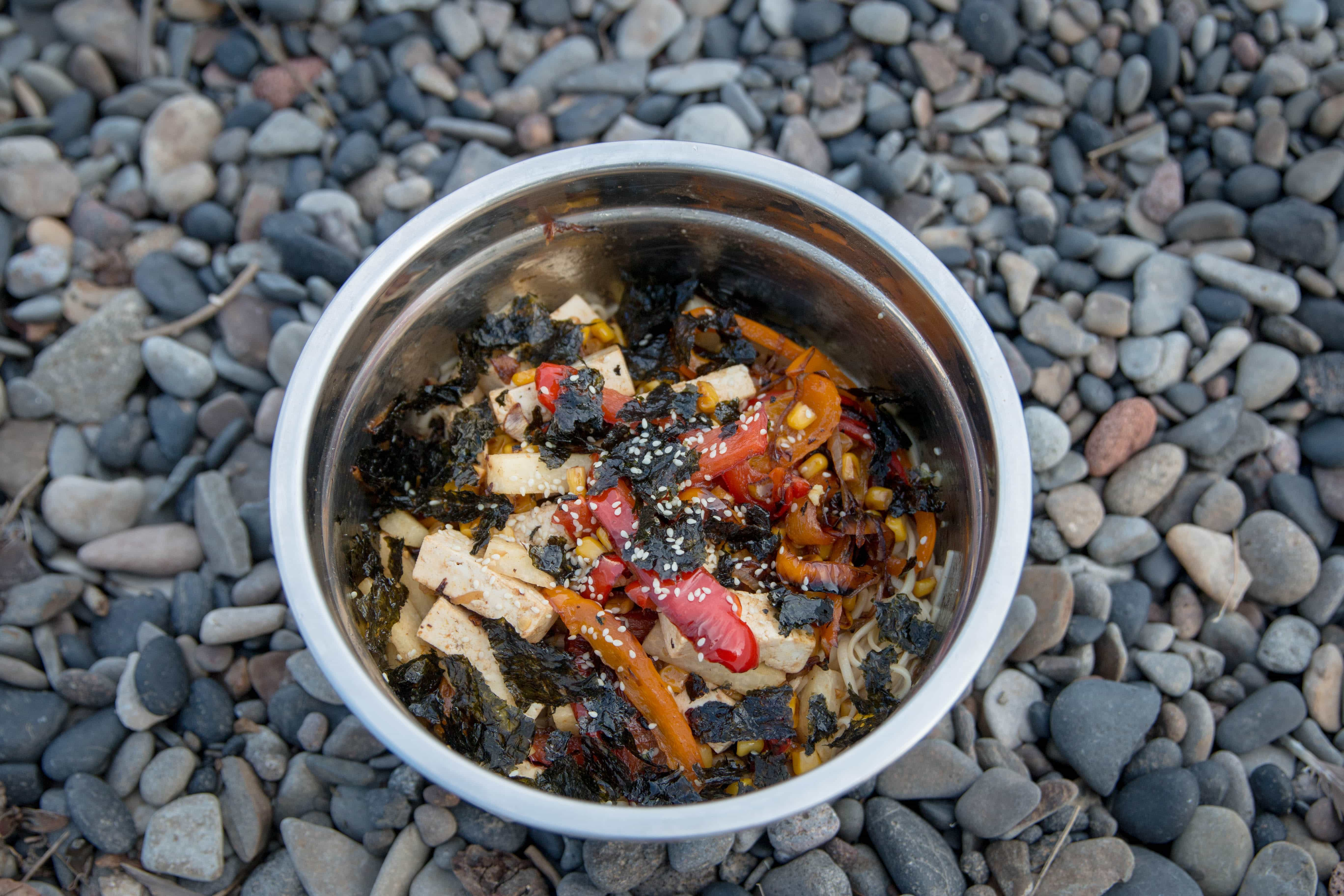 Tofu and seaweed salad in a bowl on a rocky surface
