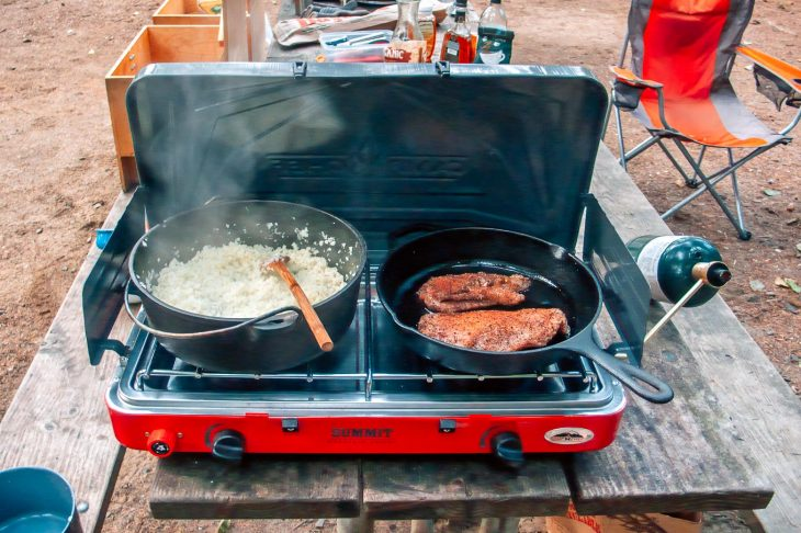 A large pot and a cast iron skillet on a red two burner camping stove