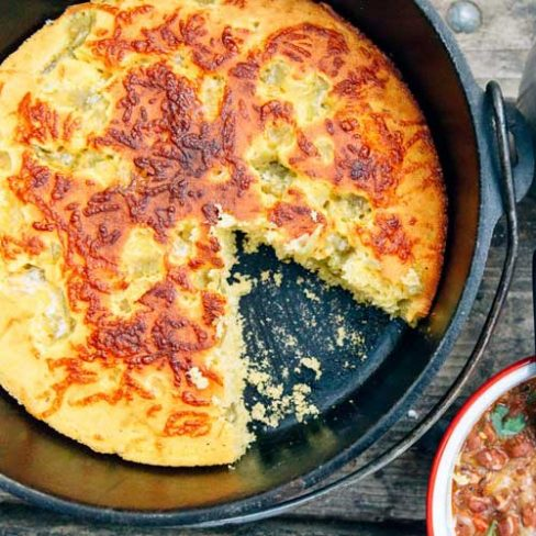 Cornbread in a Dutch oven with a slice taken out