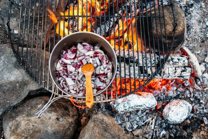 A pot of red onions over a campfire