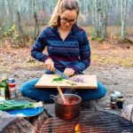 Megan sitting in front of a campfire, cutting onions on a cutting board.