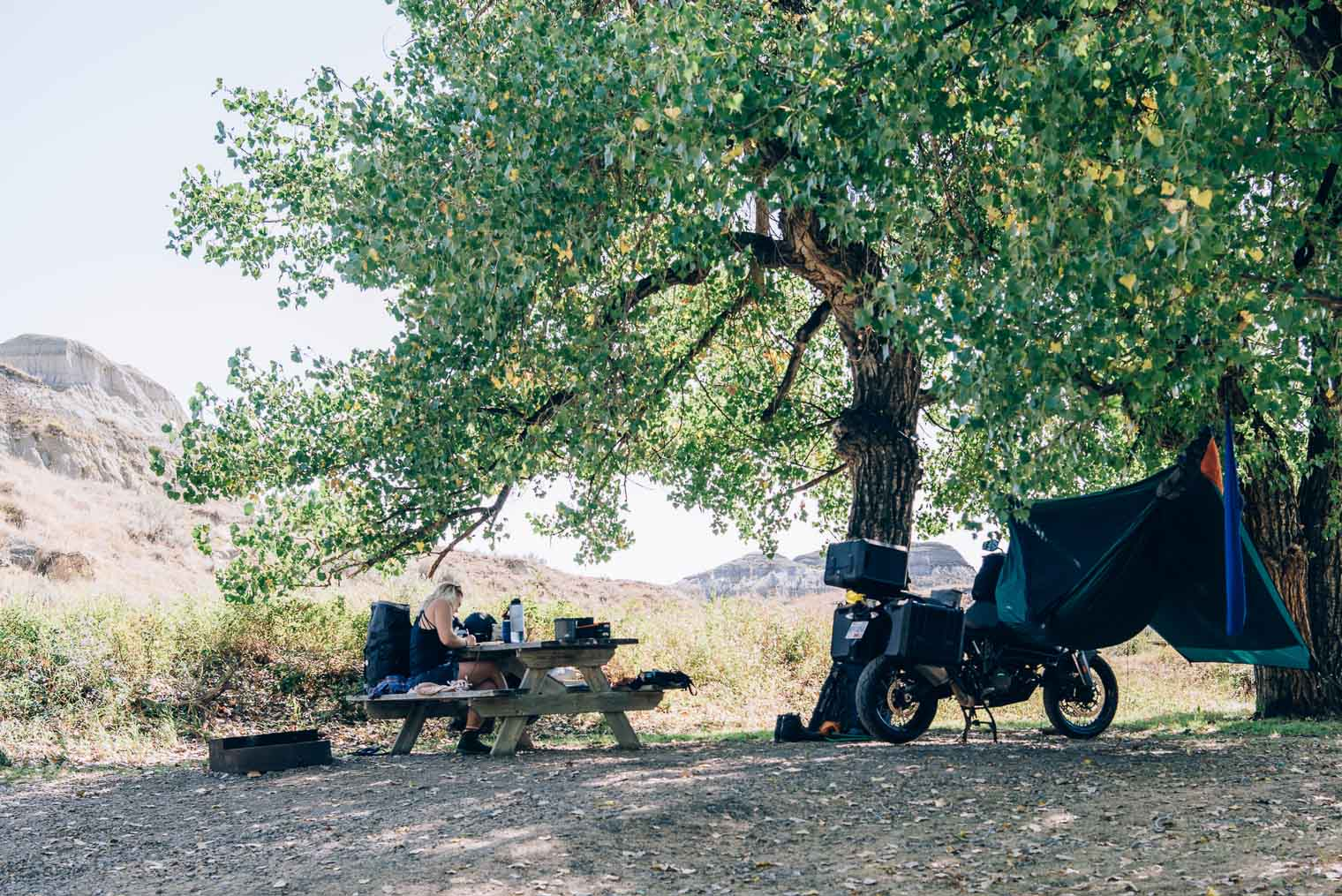 A campground with a hammock, motorcycle, and woman sitting at a picnic table