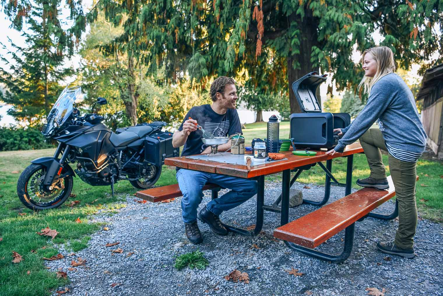 A couple eating at a picnic table with a motorcycle in the background
