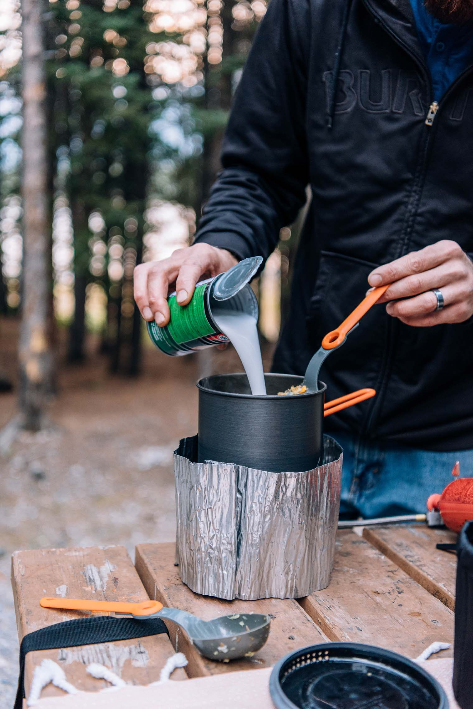 Pouring coconut milk into a pot on a camp stove