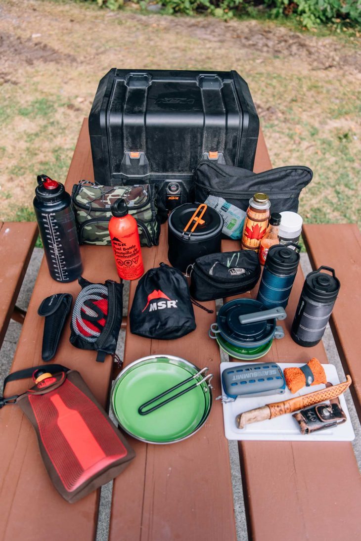 Kitchen gear for motorcycle camping laid out on a picnic table