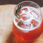 A glass of plum prosecco spritz with a sprig of rosemary