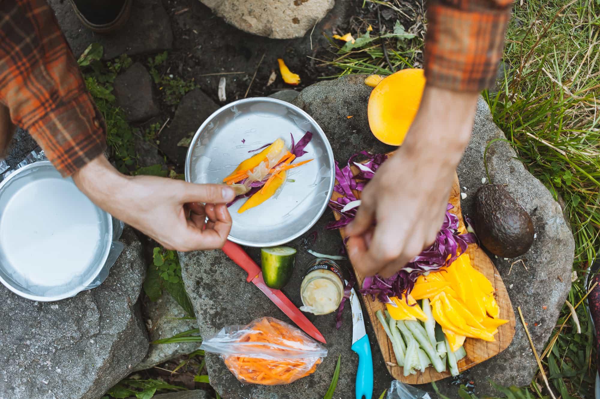 Hands assembling a fresh spring roll