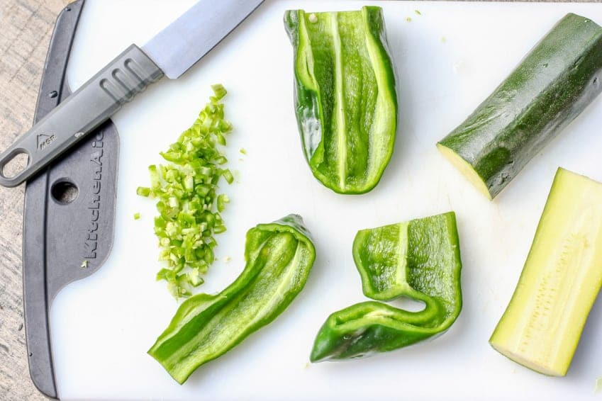 Poblano peppers and zucchinis on a white cutting board