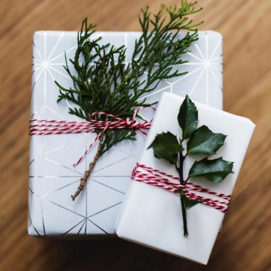 Two boxes wrapped in white paper with red ribbons and holly branches.