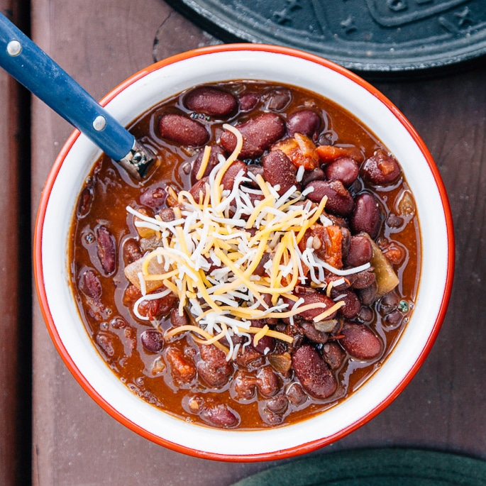 Chili in a white and red bowl topped with shredded cheese.