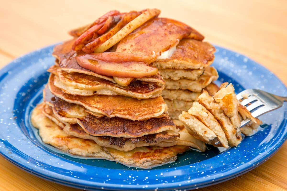 A stack of pancakes with cinnamon apples on top