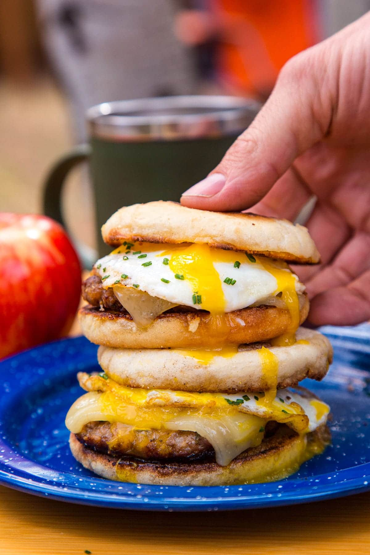 Two stacked breakfast sandwiches on a blue plate. A hand is picking one up.