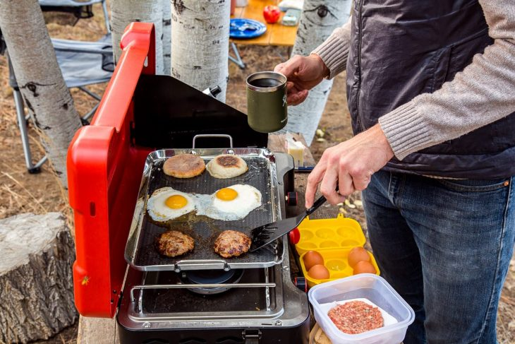 Michael is holding a mug of coffee in one hand and is holding a spatula to flip a sausage on a griddle with the other hand.