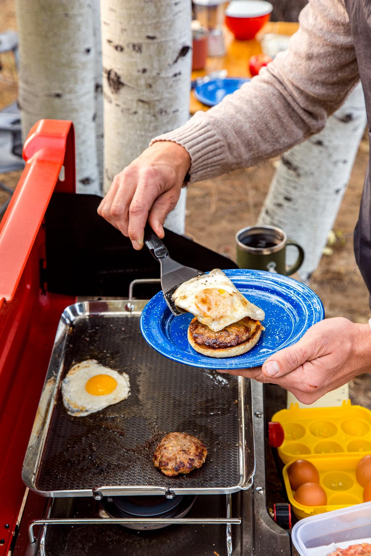 Michael is holding a plate with an english muffin and sausage on it. He is using a spatula to place an egg on top.